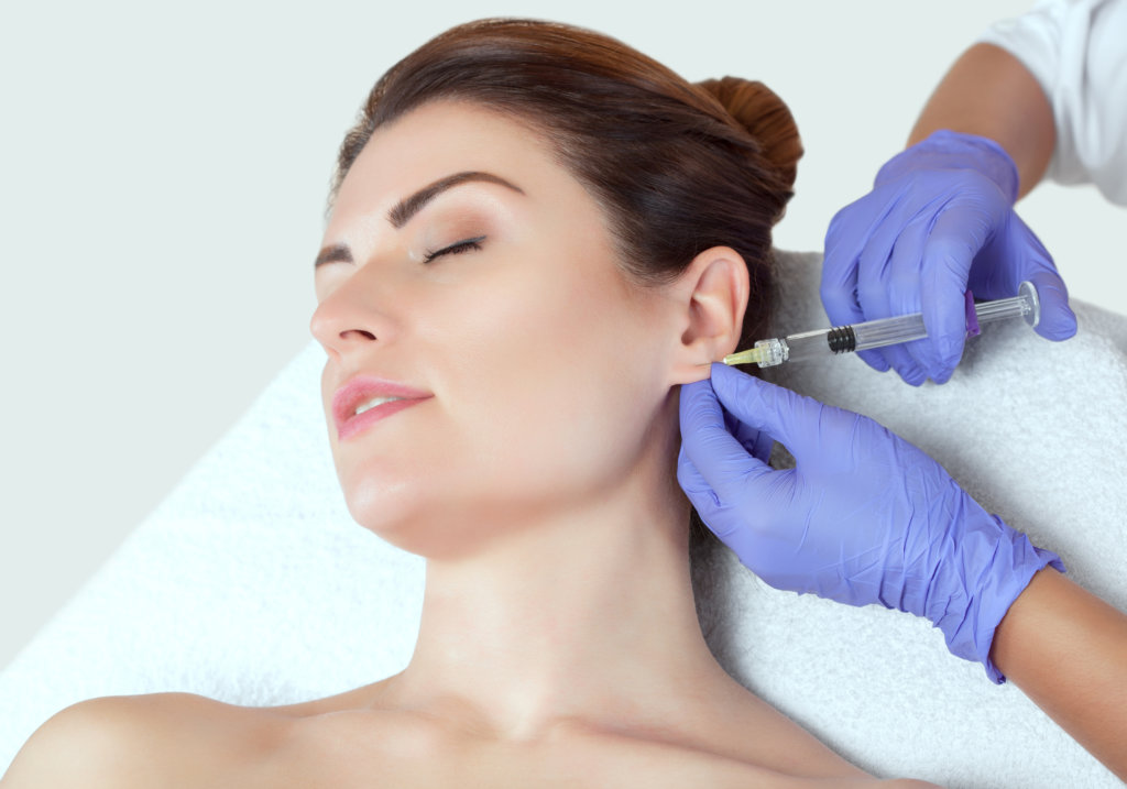 The doctor cosmetologist makes the injections procedure for smoothing wrinkles and against flabbiness of the skin on earlobe of a beautiful, young woman in a beauty salon.